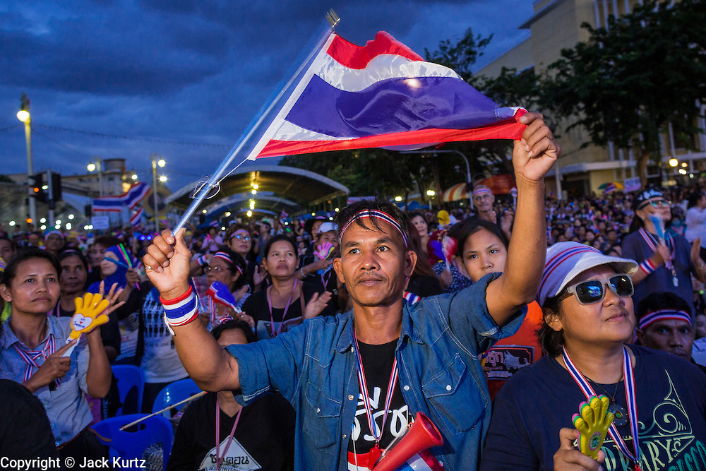 "15 NOVEMBER 2013 - BANGKOK, THAILAND:  An anti-government protester waves the Thai flag at Democracy Monument. Tens of thousands of Thais packed the area around Democracy Monument in the old part of Bangkok Friday night to protest against efforts by the ruling Pheu Thai party to pass an amnesty bill that could lead to the return of former Prime Minister Thaksin Shinawatra. Protest leader and former Deputy Prime Minister Suthep Thaugsuban announced an all-out drive to eradicate the ""Thaksin regime."" The protest Friday was the biggest since the amnesty bill issue percolated back into the public consciousness. The anti-government protesters have vowed to continue their protests even though the Thai Senate voted down the bill, thus killing it for at least six months.    PHOTO BY JACK KURTZ"