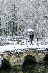 © Licensed to London News Pictures 01/02/2019, Bibury, Cirencester, UK. Tourists cross the river near Arlington row in Bibury, The Cotswolds taking photos adn enjoying the snowfall. Photo Credit : Stephen Shepherd/LNP
