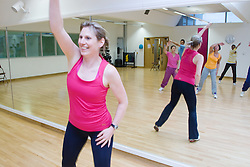 Fitness instructor leading an aerobics class at sports leisure centre,