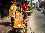 "07 FEBRUARY 2016 - BANGKOK, THAILAND: People burn ""ghost money"" to make merit for Chinese New Year in Bangkok's Chinatown. Chinese New Year, also called Lunar New Year or Tet (in Vietnamese communities) starts Monday February 8. The coming year will be the ""Year of the Monkey."" Thailand has the largest overseas Chinese population in the world; about 14 percent of Thais are of Chinese ancestry and some Chinese holidays, especially Chinese New Year, are widely celebrated in Thailand.        PHOTO BY JACK KURTZ"