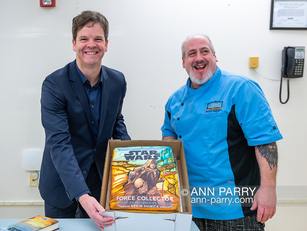 Merrick, New York, U.S. December 20, 2019. L-R, Author KEVIN SHINICK and his childhood friend BRIAN FISHMAN hold up cake Fishman, of Sweet Karma Desserts, decorated with cover of Shinick's book STAR WARS: FORCE COLLECTOR during book signing at North Merrick Library on Nassau County Force Collector Day. Author Shinick named home planet of Karr Nuq Sin, the main character of this canon Star Wars young adult novel, MEROKIA in honor of Merokee tribe who settled his Merrick hometown on Long Island.