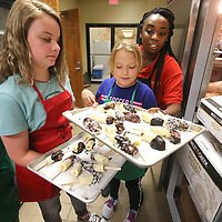 Lou Freed, 10, from Amory, Smantha Smith, 12, of Fulton and Izzy Spradlin, 10, of Mantachie, take trays of Banana pops they made from Tiara Andress, Assistant Director of the Food Service Pathway Program at ICC, as they remove them from the freezer during Culinary Camp at the ICC Belden Campus Thursday afternoon in Tupelo.