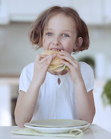 Young girl eating cheese sandwich