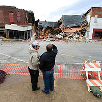 Thomas Wells | BUY AT PHOTOS.DJOURNAL.COM<br /> Okolona firefighters Cpt. Andrew McDonald, left, and Joseph Henson discuss what's left of the downtown building in Okolona following iTuesday nights high winds. The building which was already closed was expected to collapse to due it's failing structure.