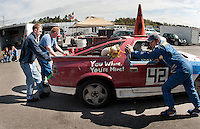Team Waahmbulance gives their car some TLC to get it back out onto the track Sunday afternoon during the 24 Hours of Lemons race at New Hampshire Motor Speedway in Loudon.  (Karen Bobotas/for the Concord Monitor)