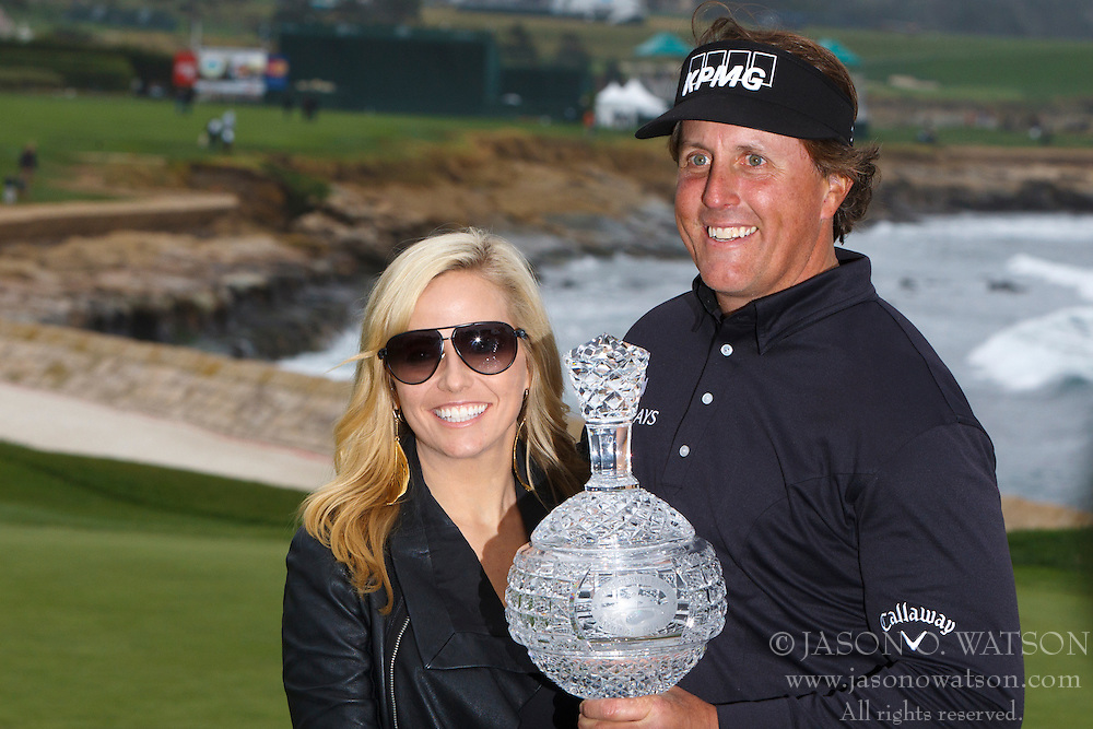 Feb 12, 2012; Pebble Beach CA, USA; Phil Mickelson (right) holds the championship trophy with his wife Amy Mickelson (left) after the final round of the AT&T Pebble Beach Pro-Am at Pebble Beach Golf Links. Mandatory Credit: Jason O. Watson-US PRESSWIRE