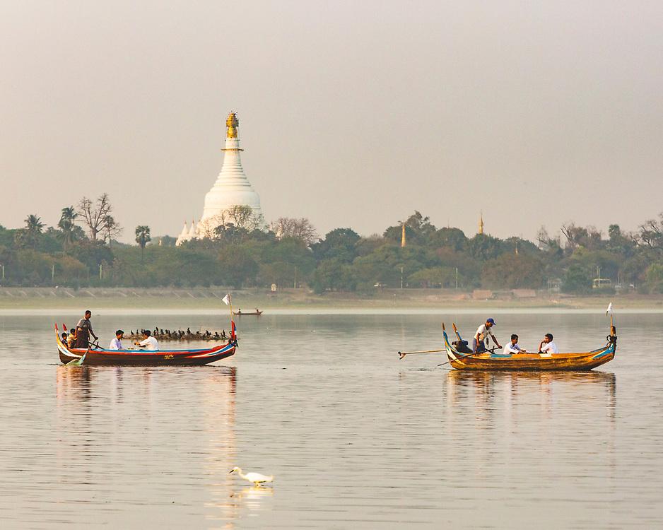 Boats in the evening light near to teh U-Bein bridge on Taung Tha Man Lake, Mandalay, Myanmar