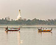 Boats in the evening light near to teh U-Bein bridge on Taung Tha Man Lake, Mandalay, Myanmar