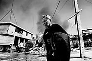 Haiti Earthquake, Port au Prince.<br /> Woman on the street where trash is burned.