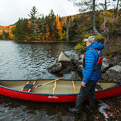 A man canoeing on Greenough Pond in Wentworths Location, New Hampshire. Fall. Northern Forest.