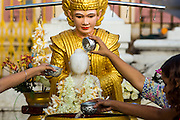 15 JUNE 2013 - YANGON, MYANMAR: People bathe a statue of the Buddha to make merit at Shwedagon Pagoda. The Shwedagon Pagoda is officially known as Shwedagon Zedi Daw and is also called the Great Dagon Pagoda or the Golden Pagoda. It is a 99 metres (325 ft) tall pagoda and stupa located in Yangon, Burma. The pagoda lies to the west of on Singuttara Hill, and dominates the skyline of the city. It is the most sacred Buddhist pagoda in Myanmar and contains relics of the past four Buddhas enshrined: the staff of Kakusandha, the water filter of Koṇāgamana, a piece of the robe of Kassapa and eight strands of hair fromGautama, the historical Buddha. The pagoda was built between the 6th and 10th centuries by the Mon people, who used to dominate the area around what is now Yangon (Rangoon). The pagoda has been renovated numerous times through the centuries. Millions of Burmese and tens of thousands of tourists visit the pagoda every year, which is the most visited site in Yangon.  PHOTO BY JACK KURTZ