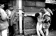 A woman supports drunken man as drinkers look on outside a pub in Cardiff on the day of the Rugby International 1989