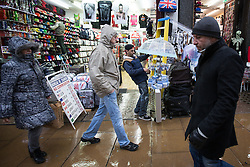 © Licensed to London News Pictures . 04/01/2014 . London , UK . A shop keeper raises an umbrella to protect his stock from the rain . Shoppers and tourists brave the wind and rain on London's Oxford Street today (Saturday 4th January 2013) as the January Sales continue . Photo credit : Joel Goodman/LNP