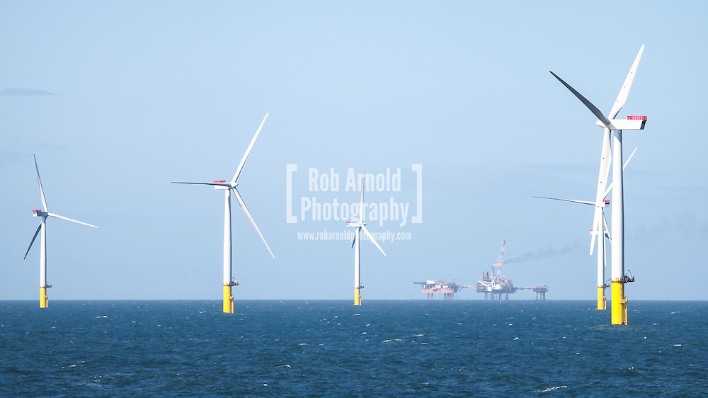 © Rob Arnold.  08/04/2014. North Wales, UK. Wind turbines of the Gwynt y Môr Offshore Wind Farm, with the oil platforms of the Douglas Complex, operated by BHP Billiton, visible in the distance. The flare stack can be seen burning. Photo credit : Rob Arnold
