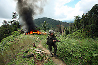 A member of the Jungla, a unit of the Colombian anti-narcotics police, keeps watch after destroying a drug lab in a coca field in the Colombian state of Bolivar, on July 3, 2007. (Photo/Scott Dalton)