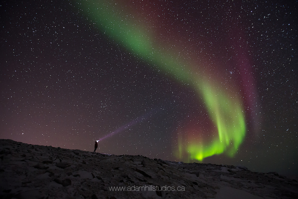 An aurora hunter stands on Second Hill in Ulukhaktok, NT.