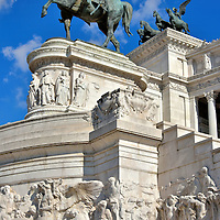 Equestrian Statue at Altare della Patria, in Rome, Italy<br /> This bronze equestrian statue by Emilio Gallori represents King Vittorio Emanuele II. He is known as Padre della Patria or Father of the Fatherland for unifying Italy in 1861. Behind him is a chariot with the winged goddess of Victory and below him are reliefs carved in Botticino marble. Look closely at the female figure on the right below the horse&rsquo;s feet. She is holding a laurel which is symbolic of peace. Similar allegories across the monument represent victory, sacrifice, and strength.