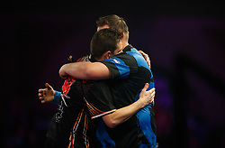Toni Alcinas is congratulated on his victory by Kevin Munch (right) during day eleven of the William Hill World Darts Championship at Alexandra Palace, London.