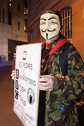 "London, December 23rd 2014. Online activism group Anonymous march through London from the City to the BBC's HQ on Great Portland Street in protest against alleged biases and coverups of a ""paedophile ring"". PICTURED: An activist protests against the BBC's ""unjust and outdated TV licence fee""."