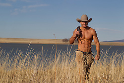 great looking shirtless cowboy walking in a field by a lake