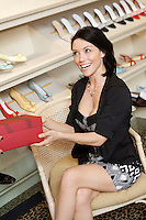 Cheerful mid adult woman with footwear box in shoe store
