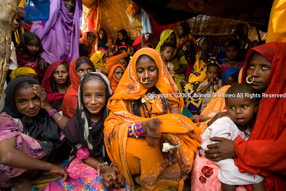 The bride and women gather at a wedding celebration of the Shanabla tribe near El Obeid, Sudan. The bride is in orange.