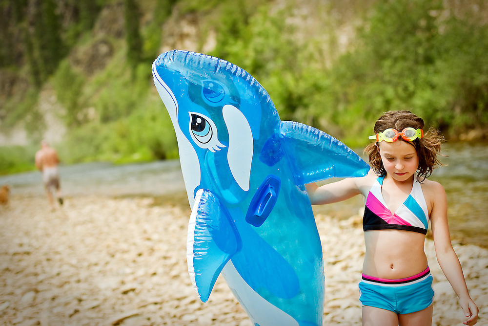 Taylor Wenglikowski carries a large inflatable dolphin along the beach during an outing to Little Bumblebee Creek on Sunday, July 11, 2010.