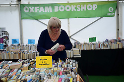 © London News Pictures. 26/05/2016. Hay on Wye, UK. The opening day of the Hay Festival 2016, and a woman sorts out the second hand books in the Oxfam store on the festival site. Photo credit: Keith Morris/LNP