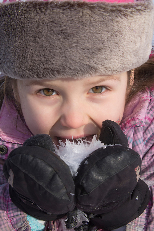 A close up shot of a young girl tasteing ice flakes on a winter afternoon. MR