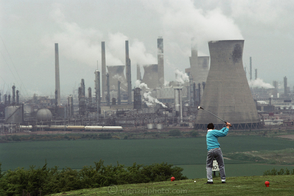 A golfer teeing off at a golfcourse overlooking the oil refinery at Grangemouth, Scotland.