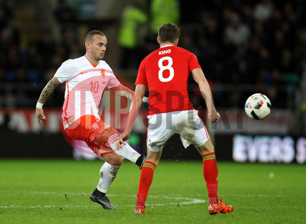 Wesley Sneijder of The Netherlands passes the ball past Andy King of Wales - Mandatory byline: Robbie Stephenson/JMP - 07966 386802 - 13/11/2015 - FOOTBALL - Cardiff City Stadium - Cardiff, Wales - Wales v Netherlands - International Friendly