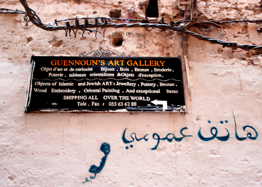 Wall sign outside Gennoun's heritage shop in Fes.  Board in English; graffiti painted on the wall below in Arabic with picture of a telephone receiver.  Thickly twisted electyric cables above bolted to the plaster wall.