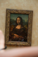 Perspective shot which appears to show someone holding the Mona Lisa