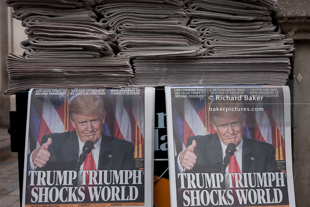 """US president-elect, Donald Trump appears on the front page of the London Evening Standard newspaper, on the day of his election, on November 9th 2016, in central London, England. The headline reads """"Trump Triumph Shocks World"""" and Londoners of all colours and races take the free paper to read the latest overnight news. (Photo by Richard Baker / In Pictures via Getty Images)"""