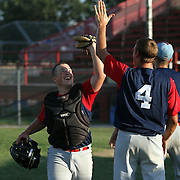 A's catcher Garrett Campfield gets a high five from teammate Corey Cowan prior to their game last June against the Omaha Diamond Spirit.  photo by David Peterson