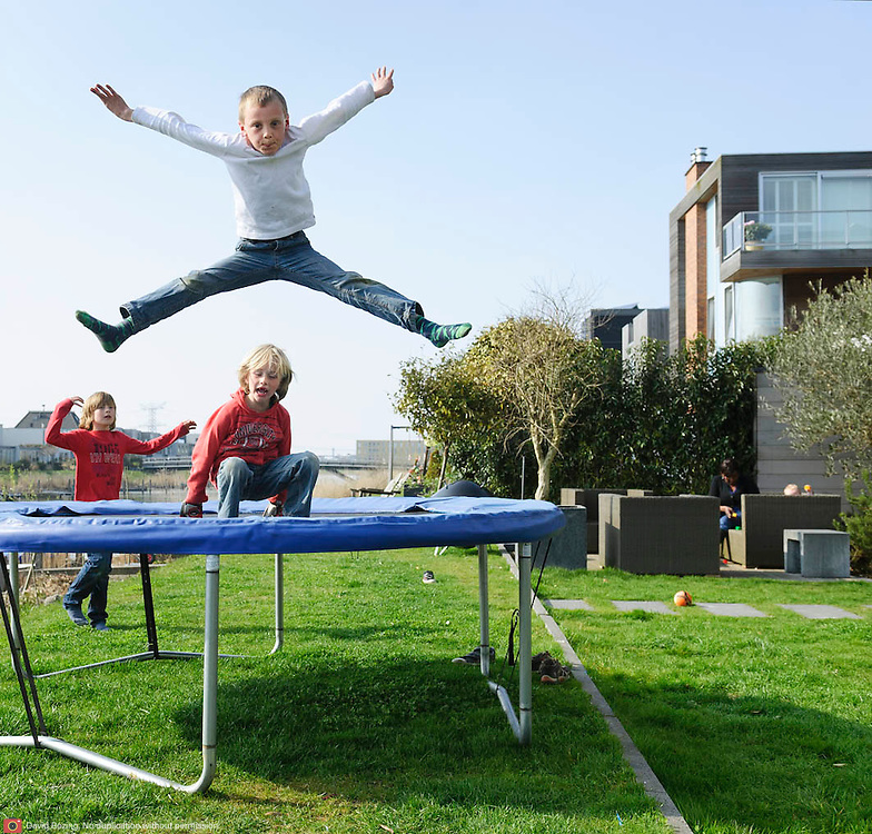 Nederland Amsterdam 29 maart 2011 20110329 Nieuwbouwwijk Ijburg, kinderen spelen, zij springen op een trampoline, in de achtertuin van een van de grote woningen met individuele architectuur die aan het water grenzen. Individueel vormgegeven architectuur. Noot: Fotograaf heeft toestemming gekregen van volwassene op de achtergrond om de beelden te maken.  Foto: David Rozing