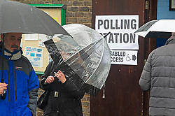 ©Licensed to London News Pictures 12/12/2019. <br /> Bromley ,UK. Umbrellas up for these voters. People battle against the wet weather to vote in the UK General Election at St Augustine scout hall, Bromley, South East London.          Photo credit: Grant Falvey/LNP