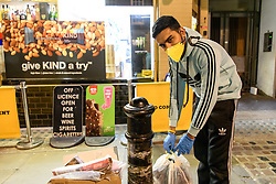 © Licensed to London News Pictures. 20/03/2020. London, UK. A shop worker brings out rubbish from one of few shops still open at 8.50pm. The West End was left unprecedentedly empty on Friday night following the government's announcement that all bars, pubs and restaurants must be closed immediately in the latest step to curb the coronavirus outbreak.  Photo credit: Guilhem Baker/LNP