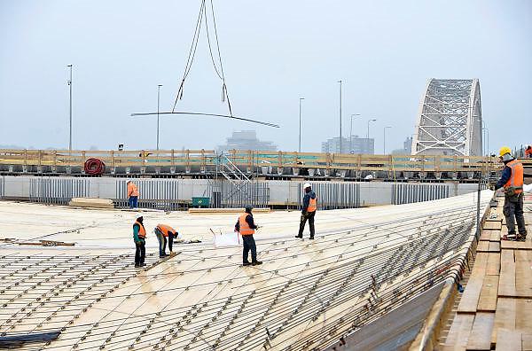 Nederland, Nijmegen, 29-10-2014 Aan de overkant van de Waal bij Lent wordt druk gewerkt aan het creeren van een nevengeul in de rivier om bij hoogwater een betere waterafvoer te hebben. Het is een omvangrijk project waarbij onder meer de pijlers van het spoorviaduct een bredere basis moeten krijgen omdat die straks in de loop van het water staan. Ook de n325 die vanaf de Waalbrug naar Arnhem loopt moet over 400 meter opnieuw worden aangelegd omdat het talud vervangen wordt door pijlers (foto). De weg wordt via een bypass omgeleid. Het dorp veurlent komt op een kunstmatig eiland te liggen met twee bruggen als ontsluiting. Een voetgangersbrug en de andere voor normaal verkeer. Inmiddels begint de nieuwe kade aan de noordkant van deze geul vorm te krijgen. Ruimte voor de rivier, water, waal. In de nieuwe dijk wordt een drempel gebouwd die stapsgewijs water doorlaat en bij hoogwater overloopt. Measures taken by Nijmegen to give the river Waal, Rhine, more space to flow during highwater and to prevent the risk of flooding. Room for the river. Reducing the level, waterlevel. Foto: Flip Franssen/Hollandse Hoogte