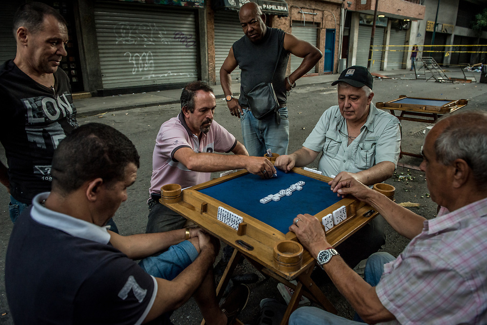CARACAS, VENEZUELA - JULY 27, 2017: Men play dominoes  infront of a line of closed businesses, while blocking the road in their neighborhood, in support of a national strike, called by the political opposition to last for  48 hours, all day July 26th and 27th. They called for their supporters to close businesses, not go to work, and instead create barricades to block off their streets.  Opposition controlled areas of the country were completely shut down.  The strike was called as part of the opposition's civil resistance movement - that began on April 1st, to protest against the Socialist government's attempt to elect a new constituent assembly that will have the power to re-write the constitution, and will threaten democracy.  PHOTO: Meridith Kohut for The New York Times