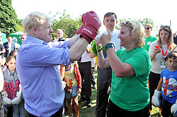 Image ©Licensed to i-Images Picture Agency. 24/07/2014. London, United Kingdom. <br /> <br /> Mayor of London Boris Johnson takes part in boxing training at Stratford Park, East London, after he announced a £1m investment in his Free Sport Programme for Londoners.<br /> <br /> Picture by Ben Stevens / i-Images