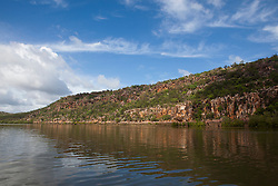 The banks of the Sale River reflected in calm water in the Kimberley wet season