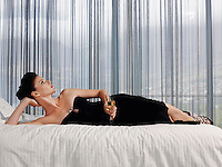 Woman wearing elegant dress lying on bed with champagne glass in bedroom