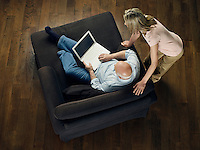 Middle-aged man sitting on sofa using laptop woman leaning and watching view from above