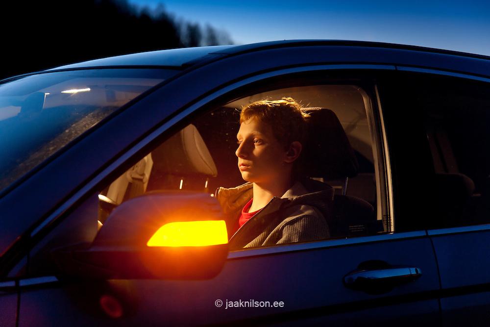 Caucasian Teenage Boy Sitting in Car at Night