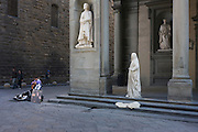 Among medieval statues, a guitarist and street busker perform for passing tourists in Florence's Piazza degli Uffizi. Dressed in white to echo the medieval figures of city officials that stand in porticos of the main Uffizi building, a man will hug any visitor who wishes to have their photo taken alongside, for the price of a few Euros. Meanwhile, to his right, the musician plays classical songs on his acoustic instrument where its sound travels around this street corner, his notes rebounding from the solid stone walls and pillars.