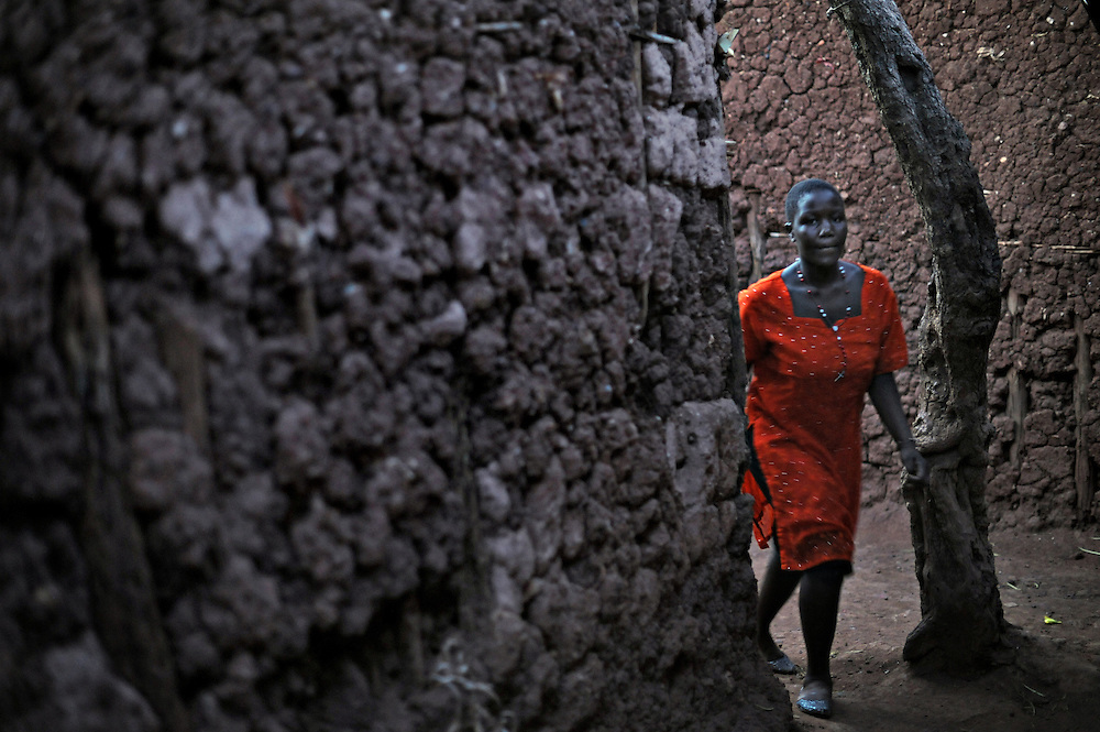 12-03-22   -- KAMPALA, UGANDA --  A woman walks through the Acholi Quarter's narrow pathways. As residents in the Acholi Quarter settle permanently, traditional northern mud dwellings are being replaced by brick homes complete with windows and doors.  Photo by Daniel Hayduk