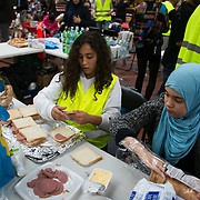 Volunteers making lunch packs. Help point at Copenhagen Central Station. An unprecedented number of refugees arrived from Germany in early September, most being Syrian war refugees, some from Afghanistan. Most wanted to travel on to Sweden and a number of Danish citizens created a spontanious network to assist the refugees with travel, food, clothes and psycological support.