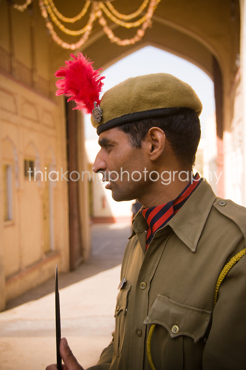 A guard stands under an archway, wearing a beret and a red feather, Jaipur, India