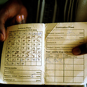 A TB patient shows her treatment card during a follow-up visit to a hospital in Homa Bay, Kenya, Friday, December 15, 2000. The card keeps track of the 8-month medication program which every patient diagnosed with TB must complete to prevent a reinfection. TB infections in Kenya<br /> are rapidly increasing due to the spread of HIV/AIDS. In Homa Bay the infection rate is 30%. <br /> <br /> Photo by Lori Waselchuk